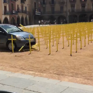 A car runs over yellow crosses in installation supporting political prisoners