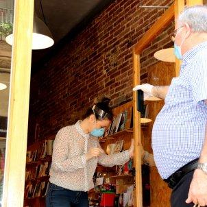 Un client ensenya la comanda feta des de la porta de la llibreria La Carbonera en el primer dia d'activitat amb cita prèvia/ACN