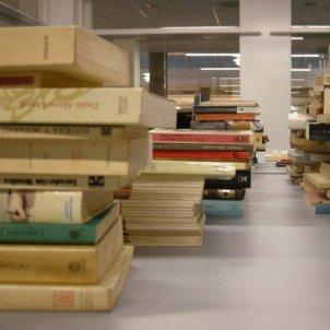Llibres apilats en una taula a la Biblioteca de la Facultat de Lletres de la UdL/ACN