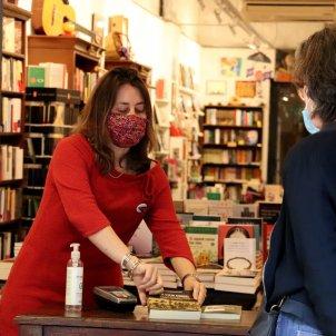 La llibretera de l'Obaga, Carol Porta, atén una clienta des de l'entrada de la llibreria en el primer dia sense cita prèvia/Mar Vila/ACN