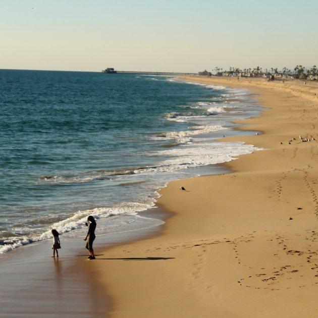 Madre e hija disfrutando de la playa de Newport, California