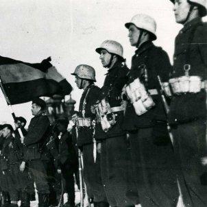 Fotografía de la bandera española presidiendo un acto de la División Azul