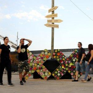 Assistents al Festival Cruïlla passen davant d'un panell del festival. Pau Cortina.