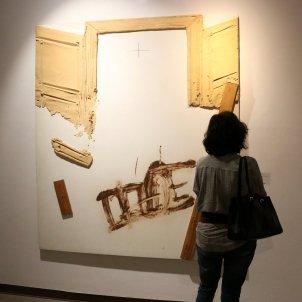 Una persona contempla un dels 11 quadres de l'exposició 'Tàpies avui'. Mar Vila ACN
