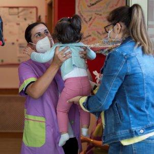 Una dona lliura a super filla a una educadora a les portes d'una escola infantil a Ourense, Galícia, aquest dimarts. Foto: Efe