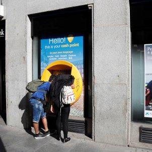 Diverses persones al centre de Madrid davant d'una sucursal de Caixabank. Foto: Efe
