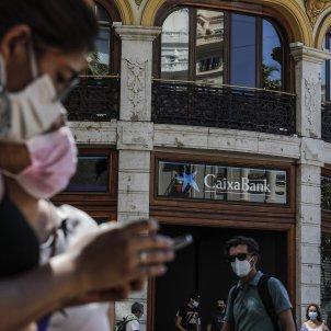 Personas pasan por las inmediaciones de la sede de Caixabank, en Valencia, Comunidad Valenciana. Foto: Europa Press