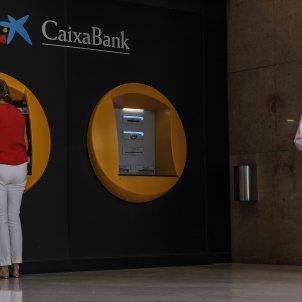Dues persones en els caixers disposats a l'edifici de la seu de Caixabank, a València, Comunitat Valenciana. Foto: Europa Press