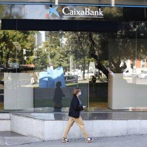Una mujer pasa por al lado de las oficinas de Caixabank en el Paseo Castellana, en Madrid (España). Foto: Europa Press