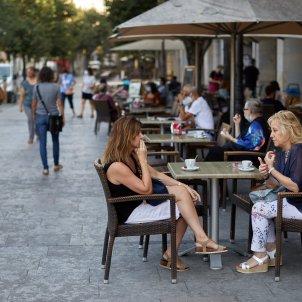 Unes clientes prenen café a la terrassa d'un bar de Girona. Foto: Efe