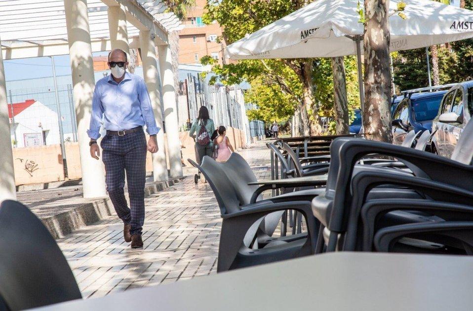 Un home camina junt a la terrassa d'un bar. Foto: Europa Press