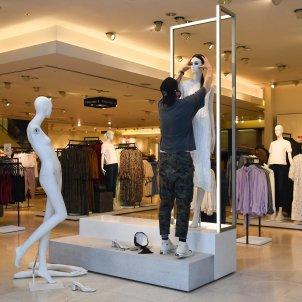 Un treballador vesteix un maniquí a una botiga de Zara. Foto: Europa Press