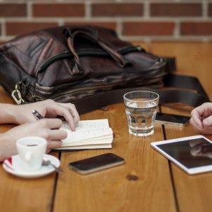 Dos usuarios trabajando en la mesa de un bar con sus dispositivos electrónicos. Foto: Pixabay
