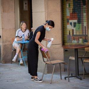 Una cambrera neteja diverses cadires i una taula de la terrassa d'un bar. Foto: Europa Press