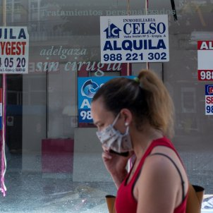 Una dona amb mascareta passa davant un comerç tancat amb diversos cartells que anuncien el seu lloguer. Foto: Efe / Brais Lorenzo / Arxiu