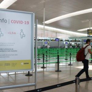 Pla general d'un cartell informatiu de la Covid-19 i d'un passatger arrossegant una maleta amb el control de seguretat de la T1 de l'Aeroport del Prat. Foto: ACN
