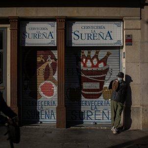 Una persona roman quieta davant d'un restaurant La Sureña en un carrer de Barcelona, Catalunya. Europa Press