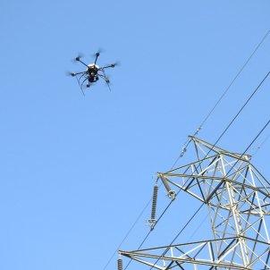 Pla detall d'un dron sobrevolant una línia elèctrica d'alta tensió. Foto: ACN
