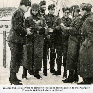 Dos guardias civiles con uniforme reglamentario controlando la documentación de cinco divisionarios Foto Biblioteca virtual del ministerio de defensa