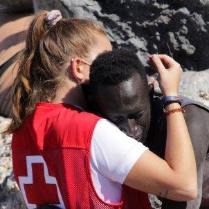 voluntaria cruz roja consuela migrante que llega / EFE