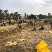 Un centenar de persones aconsegueixen plantar creus grogues a la platja de Mataró